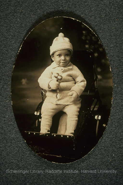 An infant seated in a stroller holding a rattle.