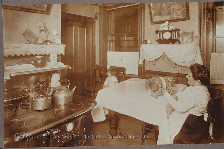 Woman in the kitchen, probably making lace, ca. 1890-1915. She is sitting at a table, wearing an apron.