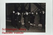 U.S. Naval officers and others, including members of the WAVES, standing at attention outdoors at the U.S. Naval Training School in the Bronx, New York.  See individual photos for additional description.