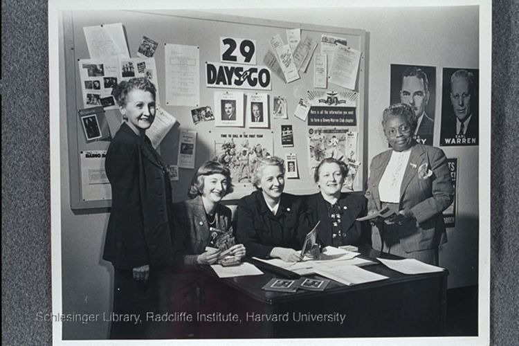 Jessica Weis (center) seated with four women, including one African American, in front of a bulletin board of material about Dewey and Warren.
