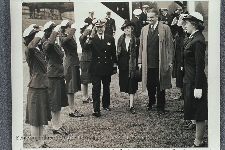 Captain William Amsden, former First Lady Grace Coolidge, and Bronx Borough President James J. Lyons walking past members of the WAVES outdoors at the Naval Training School in the Bronx, New York City. The women are saluting Captain Amsden, and he is returning the salute.