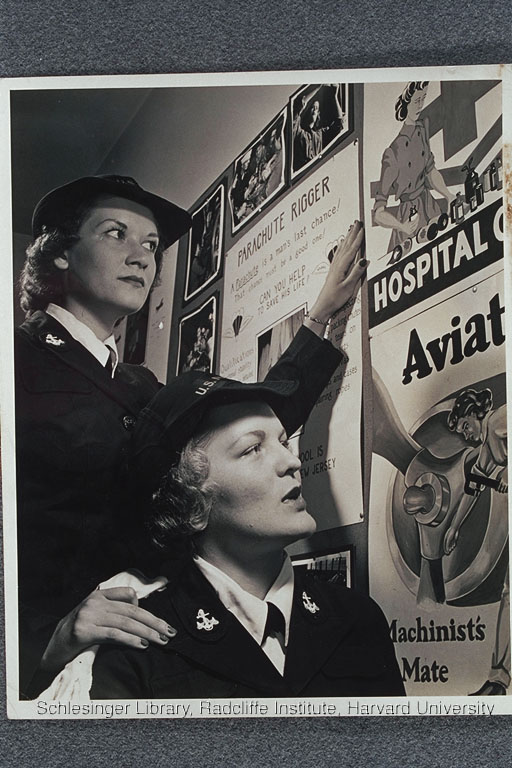 Members of the WAVES, students at the United States Naval Training School in the Bronx, looking at recruitment posters for aviation mechanics.
