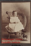 Daniel R. Pinkham as a young boy, seated in a wicker chair, with a small horse toy.  See also MC181-2903-14.
