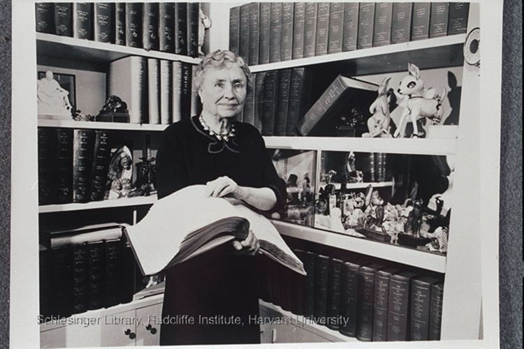 Helen Keller, reading, standing in front of a bookcase.