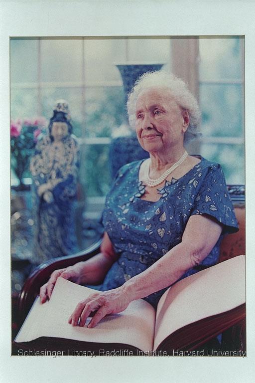 Helen Keller reading a brail book in a blue dress.