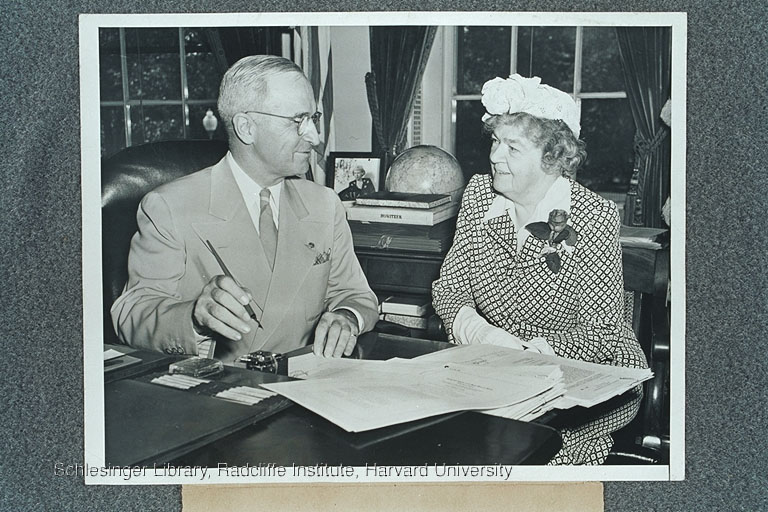 Edith Rogers seated next to President Truman at his desk in the Oval Office. She is watching him sign veterans' legislation.