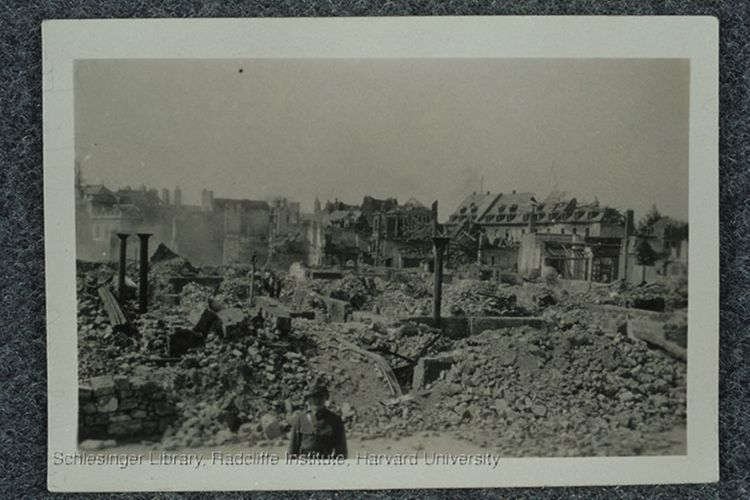 Fannie Fern Andrews standing in front of ruins in the town of Béthune. The buildings were ruined by fighting during World War I.