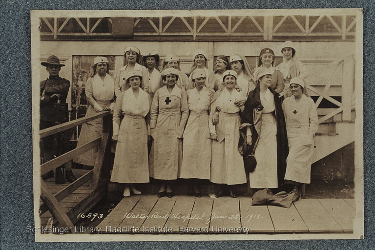 Group portrait of Red Cross nurses during World War I outside at Walter Reed Hospital. Edith Rogers is in the bottom row, second from the right. A man dressed in a military uniform with a rifle stands nearby. Possibly later copy ca. 1920-1940
