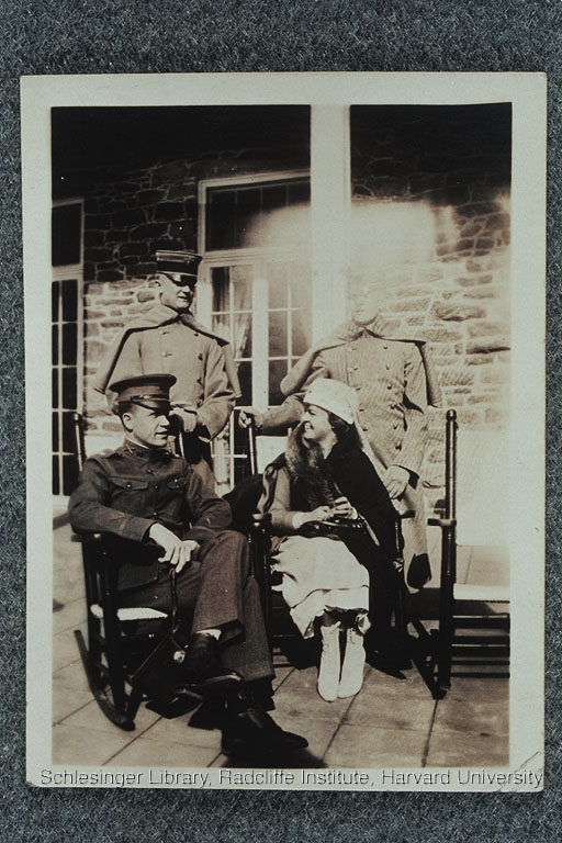 Edith Rogers, dressed in her Red Cross uniform, seated on a patio with three unidentified men Army officers.