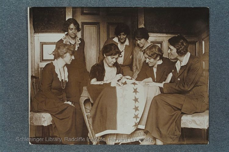Alice Paul sewing stars on the suffrage flag as others look on, ca.1920.