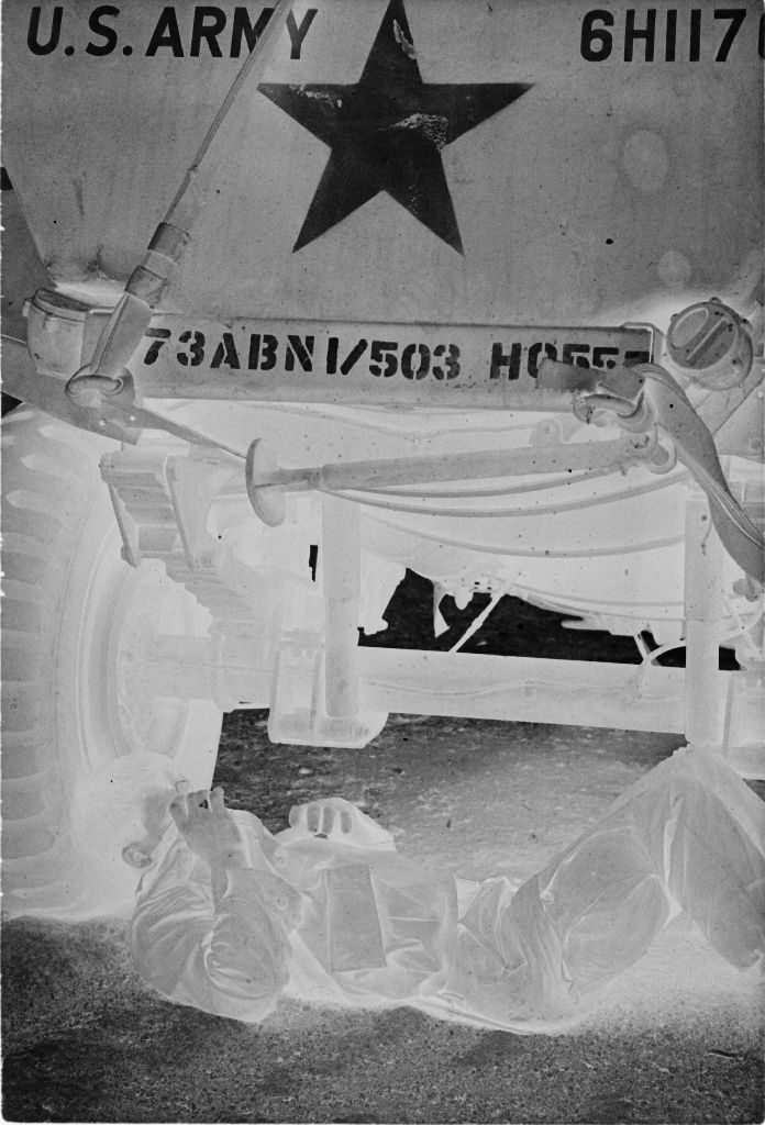 Untitled (Soldier Lying On Ground Under Army Vehicle Covering Face With Jacket, Vietnam)
