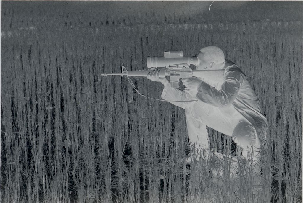 Untitled (Soldier Crouched In Rice Paddy Aiming Rifle Looking Though Sight Attachment, Vietnam)
