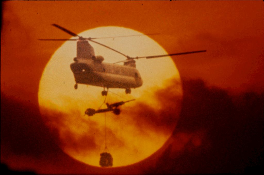 Untitled (Chinook Helicopter With Lifting 105Mm Howitzer Silhouetted Against Sun And Low Clouds, Vietnam)