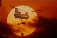 Untitled (Chinook Helicopter Lifting 105Mm Howitzer Silhouetted Against Sun, Vietnam)