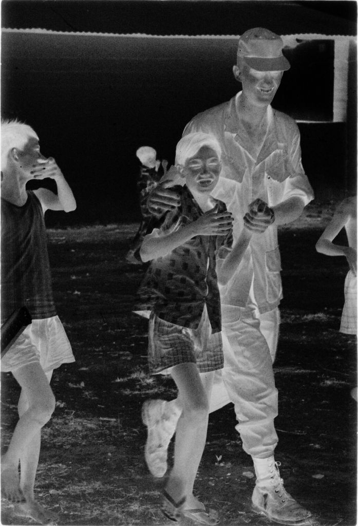 Untitled (U.s. Soldier Walking With Vietnamese Children Through Town, Gadsden Village, Vietnam)