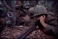 Untitled (Soldier In Combat Gear Lying On Ground With Phone Receiver To Left Ear During Fighting In Central Highlands Near Dak To, Vietnam)