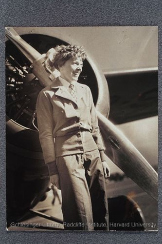 Amelia Earhart standing in front of an airplane propeller.