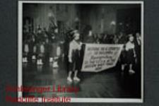 """A band of bag pipers playing at a social event.  Two young women, dressed as majorettes, are holding a banner which reads """"Restore the 6 Counties to Ireland & Recognition to the F. E. V. A. at the Boston Navy Yard.""""  The F. E. V. A. might bet the Federal Employees Veterans Association."""