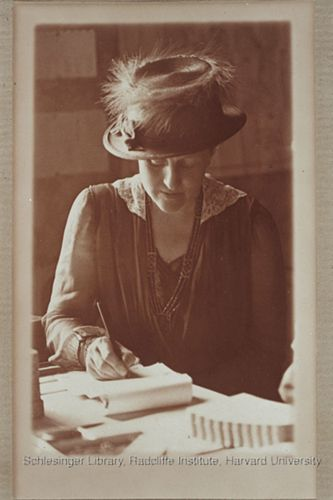 An unidentified woman seated at a desk. She is writing in a notebook.