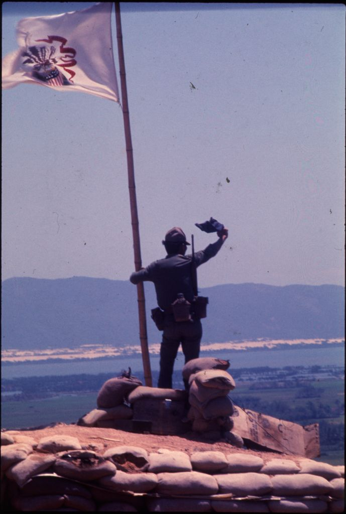 Untitled (Soldier Standing With Flag On Hilltop Overlooking Landscape, Vietnam)