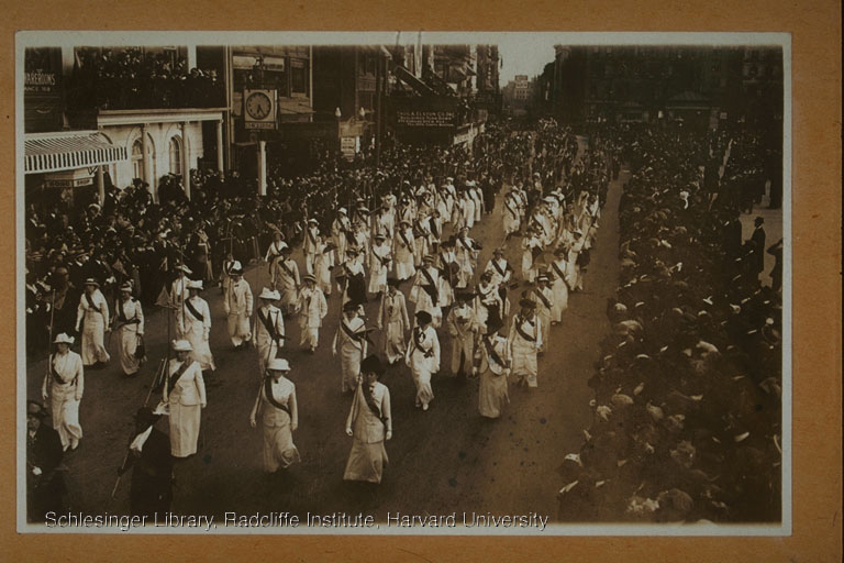 A regiment of women in uniform (white or pale clothes and a dark sash) carrying staffs and marching in formation along Beacon St. Crowds look on from both sidewalks.  Photograph. Gelatin Prints