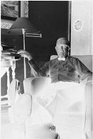 Untitled (Dr. Herman M. Juergens sitting in armchair smoking cigar)