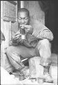Untitled (Soldier Seated In Doorway Eating From A Can, Vietnam)
