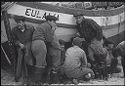 Untitled (Fishermen Crouched Around Side Of Boat, Nazaré, Portugal)