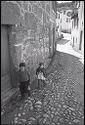 Untitled (Two Young Children Standing Near Doorway In Cobblestone Street, Nazaré, Portugal)