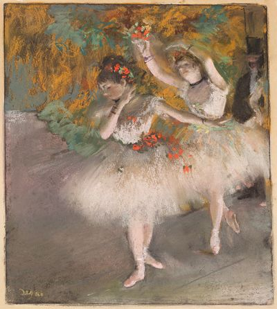 Two fair-skinned ballet dancers in tutus enter on stage from the right.