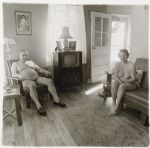 Retired man and his wife at home in a nudist camp one morning in N.J. 1963. On the television set are framed photographs of each other.
