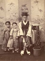 Seated Young Korean Man And Two Small Girls