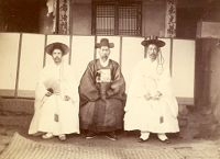 Three Korean Gentlemen Seated On The Veranda Of A House (Or Official Building)