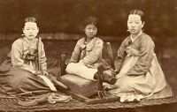 Three Young Korean Women Wearing Traditional Robes, Sitting On Mats,and Preparing To Pound Cloth
