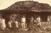 A Country Family Dressed In Traditional Robes And Standing Before A Farm House With Thatched Roof