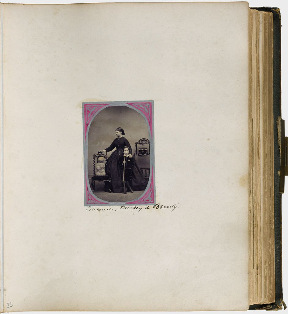 Untitled (Single Photograph Labeled Bunny, Mickie And Beauty, Woman Standing In Center Of Photograph, Left Hand On Shoulder Of Boy Holding Rifle, Dog Sitting Up In Chair To Left)