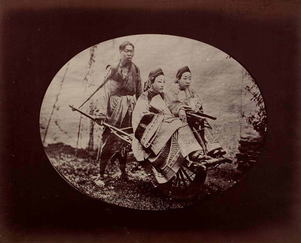Two Women Seated On A Cart Pushed By A Servant