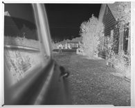 Untitled (view down side of car of man making measurements)