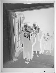 Untitled (Line Of Graduates In Caps And Gowns Carrying Flower Garland Over Shoulders)