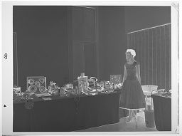 Untitled (Young Woman Standing Next To Table Of Kitchenware Gifts)