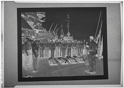 Untitled (Photograph Of Naval Funeral: Speaker And Group Of Men Around Coffins On Ship Deck)