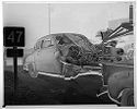 Untitled (Wrecked Car Hooked To Tow Truck On Town Street)