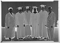 Untitled (Group Portrait Of Four People In Graduation Gowns With Man And Woman In Suits)