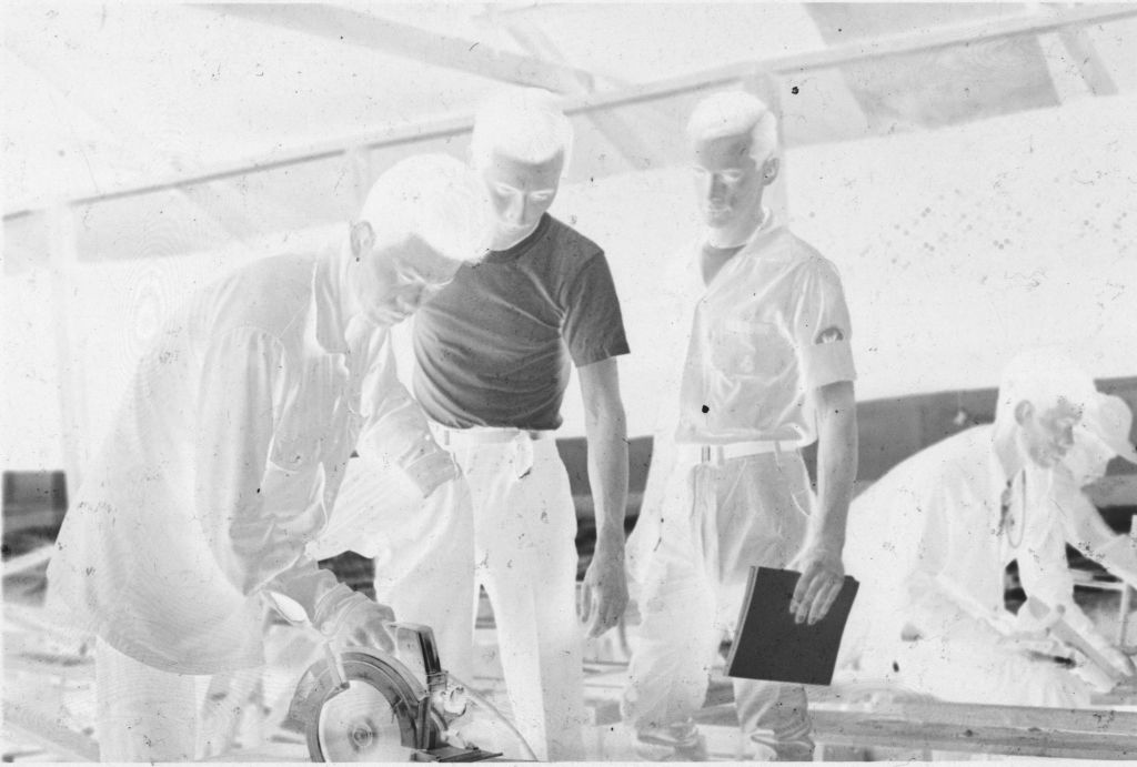 Untitled (Two U.s. Soldiers Watch While Vietnamese Soldier(?) Works With Circular Saw, Vietnam)
