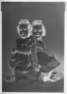 Untitled (studio portrait of two twin girls with curly hair sitting back to back)