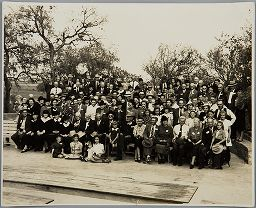 Untitled (Large Group Portrait On Curved Stone Step, Wooden Planks In Foreground, Trees Behind)