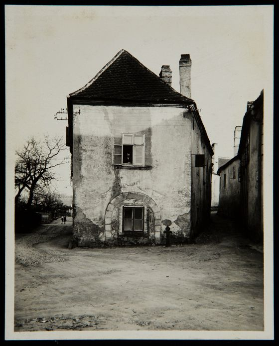 Untitled (two story house, man leaning on window sill on second ...