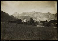 Untitled (Landscape, Landschau, Austria, Meadow In Foreground, Barn To Left Of Church On Rise, Other Buildings To Right, Mountains In Background)