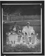 Untitled (couple sitting in upholstered chairs on lawn)