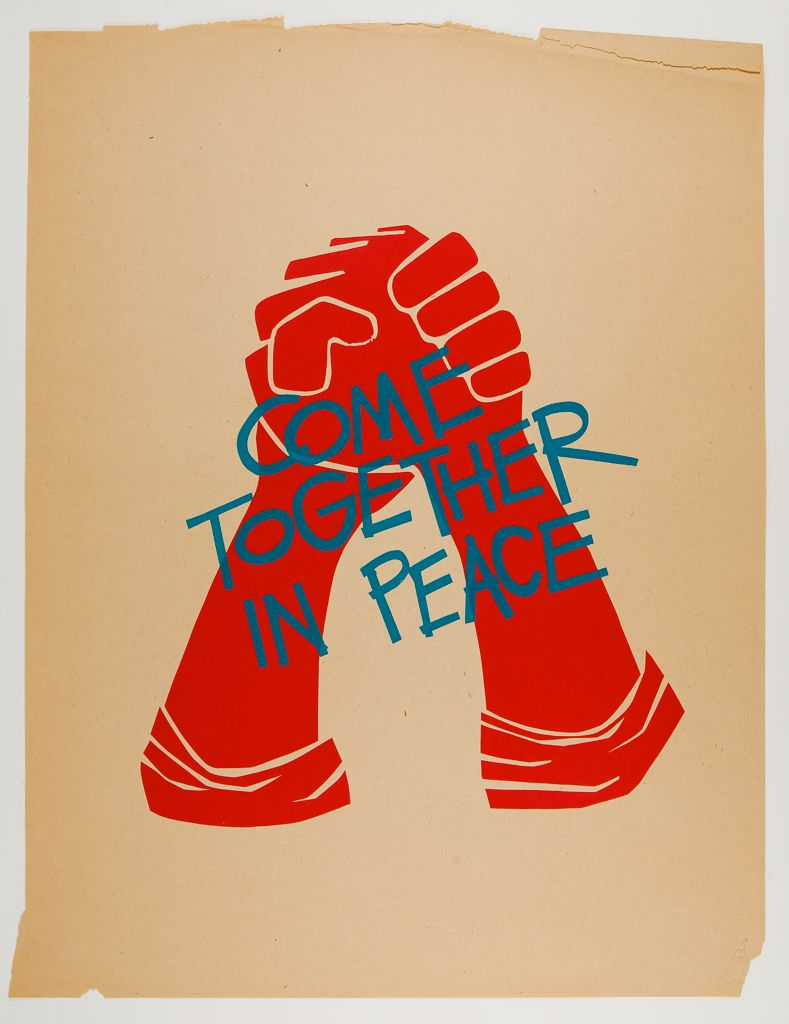 "This print shows two raised hands, clasped together, in fire engine red, overlaid with a blue inscription in all caps, ""Come Together in Peace."" The background is beige."